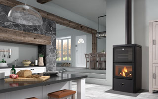 Estufa de leña encendida de Rocal en una cocina de diseño